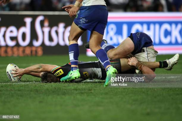 Mitch Rein of the Panthers stretches out to score a try as he is tackled by Josh Jackson of the Bulldogs during the round 13 NRL match between the...