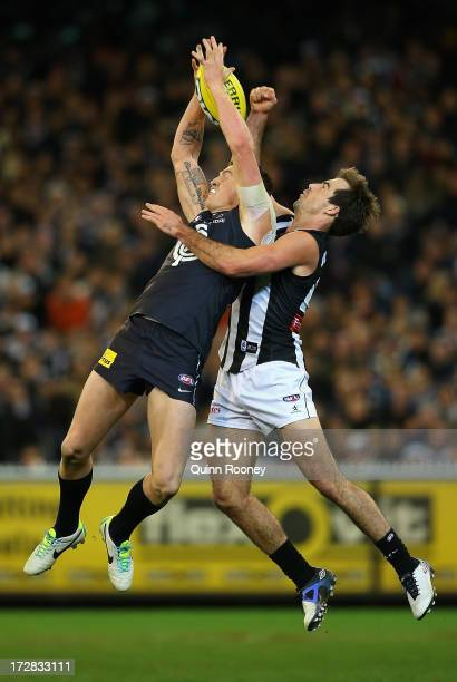 Mitch Robinson of the Blues marks infront of Steele Sidebottom of the Magpies during the round 15 AFL match between the Carlton Blues and the...
