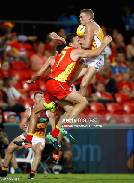 Mitch Robinson of the Lions and Steven May of the Suns compete for the ball during the 2017 AFL round 01 match between the Gold Coast Suns and the...