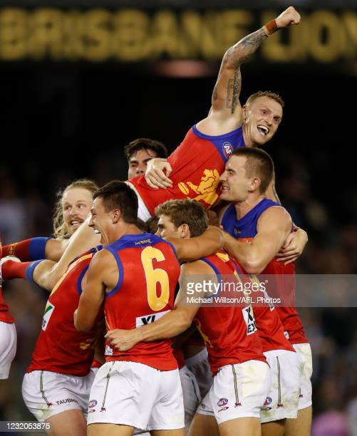Mitch Robinson of the Lions and Zac Bailey of the Lions celebrate with teammates after kicking the winning goal after the siren during the 2021 AFL...