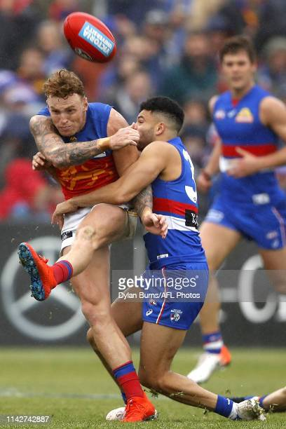 Mitch Robinson of the Lions is tackled by Jason Johannisen of the Bulldogs during the 2019 AFL round 08 match between the Western Bulldogs and the...