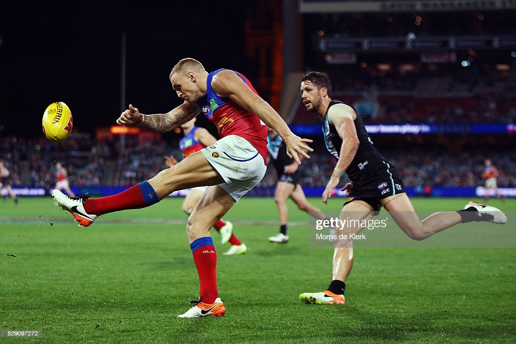 Mitch Robinson of the Lions kicks the ball in front of Travis Boak of the Power during the round seven AFL match between the Port Adelaide Power and the Brisbane Lions at Adelaide Oval on May 8, 2016 in Adelaide, Australia.