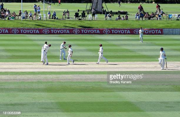 Mitch Swepson of Queensland celebrates with team mate Jimmy Peirson after taking the wicket of Baxter Holt of New South Wales during day four of the...