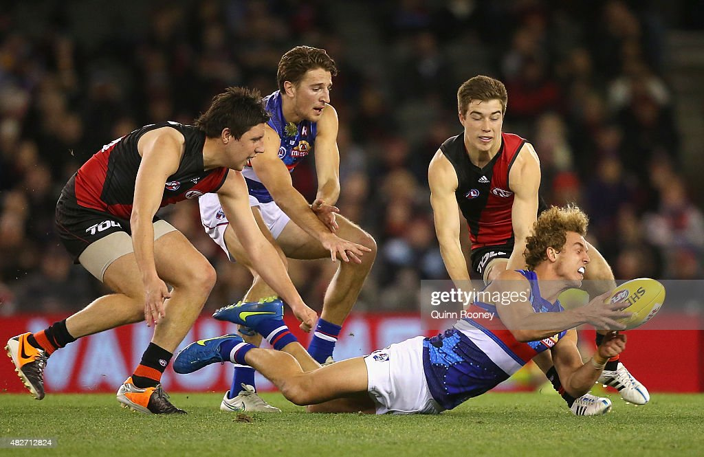 Mitch Wallis of the Bulldogs handballs whilst being tackled by Zach Merrett of the Bombers during the round 18 AFL match between the Essendon Bombers and the Western Bulldogs at Etihad Stadium on August 2, 2015 in Melbourne, Australia.