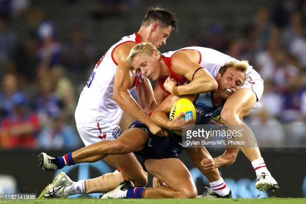 Mitch Wallis of the Bulldogs is tackled by Isaac Heeney of the Swans and Callum Sinclair of the Swans during the 2019 AFL round 01 match between the...