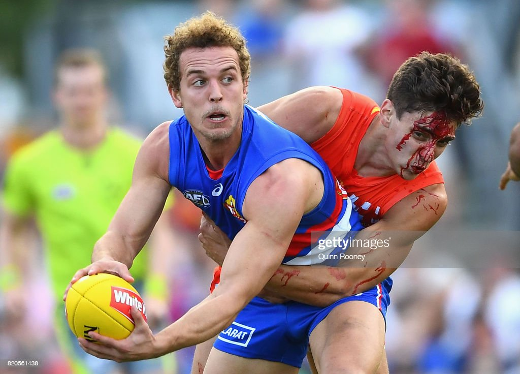 Mitch Wallis of the Bulldogs is tackled by Sean Lemmens of the Suns during the round 18 AFL match between the Western Bulldogs and the Gold Coast Titans at Cazaly's Stadium on July 22, 2017 in Cairns, Australia.