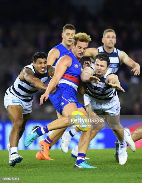 Mitch Wallis of the Bulldogs kicks whilst being tackled by Tim Kelly and Patrick Dangerfield of the Cats during the round 15 AFL match between the...