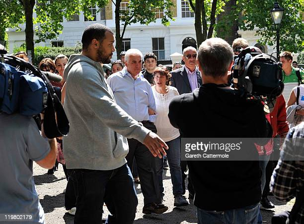 Mitch Winehouse and Janis Winehouse are surrounded by the media as they look at floral tributes at Amy's house by fans on July 25 2011 in London...