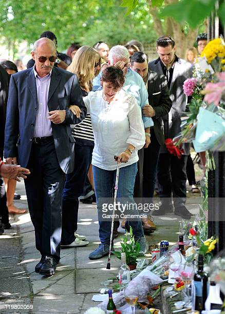 Mitch Winehouse and Janis Winehouse look at floral tributes with their son Alex Winehouse and Amy's former boyfriend Reg Traviss at Amy's house by...