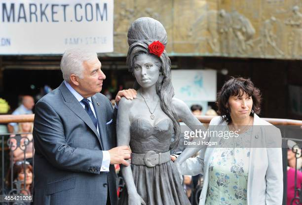 Mitch Winehouse and Janis Winehouse pose as a statue of the late Amy Winehouse is unveiled in Camden Town on September 14 2014 in London England