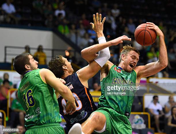 Mitch Young of the Crocodiles grabs rebound over Alex Loughton of the Taipans during the round nine NBL match between the Townsville Crocodiles and...