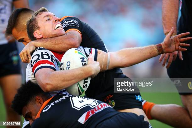 Mitchell Aubusson of the Roosters is tackled by Luke Brooks and Kevin Naiqama of the Tigers during the round one NRL match between the Wests Tigers...