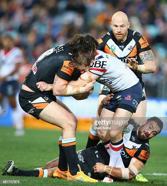 Mitchell Aubusson of the Roosters is tackled during the round 20 NRL match between the Wests Tigers and the Sydney Roosters at ANZ Stadium on July 24...