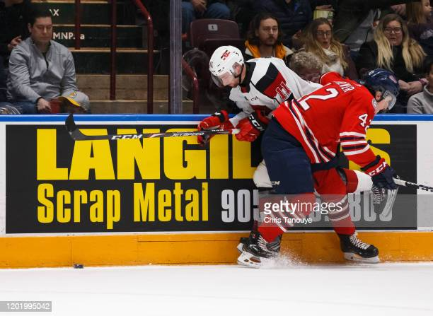 Mitchell Brewer of the Oshawa Generals bodychecks Adam Varga of the Ottawa 67's during an OHL game at the Tribute Communities Centre on January 19,...
