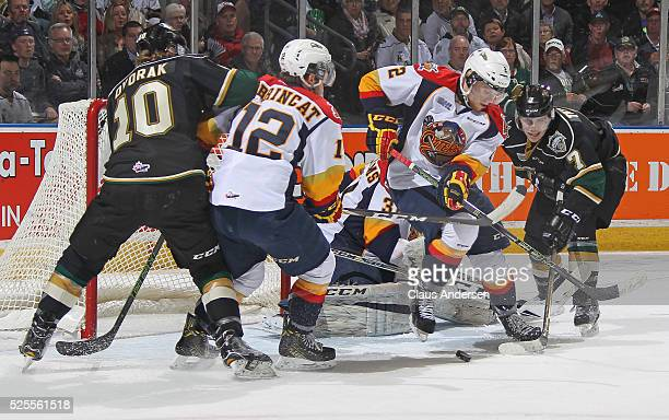 Mitchell Byrne of the Erie Otters looks to clear a puck away from Matthew Tkachuk of the London Knights during game four of the OHL Western...