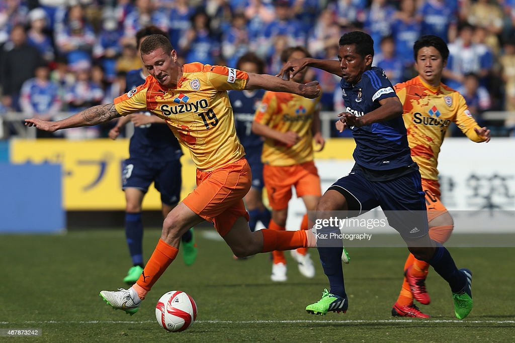 Mitchell Duke of Shimizu S-Pulse and Fabio of Yokohama F.Marinos compete for the ball during the J.League Yamazaki Nabisco Cup match between Yokohama F.Marinos and Shimizu S-Pulse at Nippatsu Mitsuzawa Stadium on March 28, 2015 in Yokohama, Kanagawa, Japan.