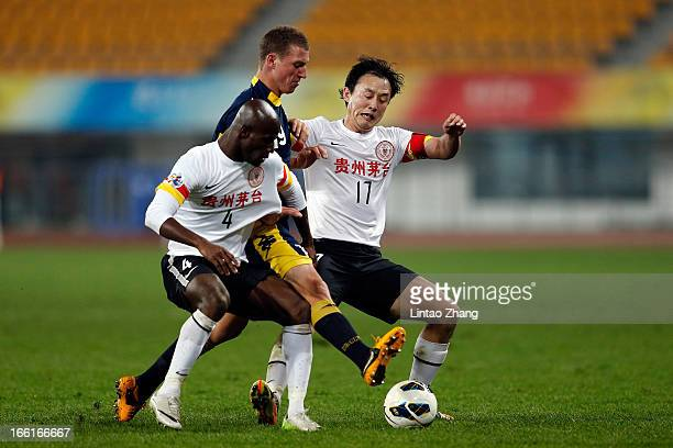 Mitchell Duke of the Mariners challenges Jonas Salley and Sun Jihai of Guizhou Renhe during the AFC Champions League match between Guizhou Renhe and...