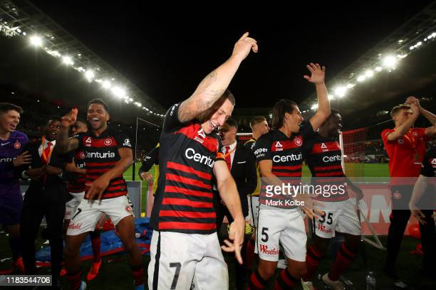 Mitchell Duke of the Wanderers and his team mates dance as they celebrate with the crowd after victory during the round three A-League match between...