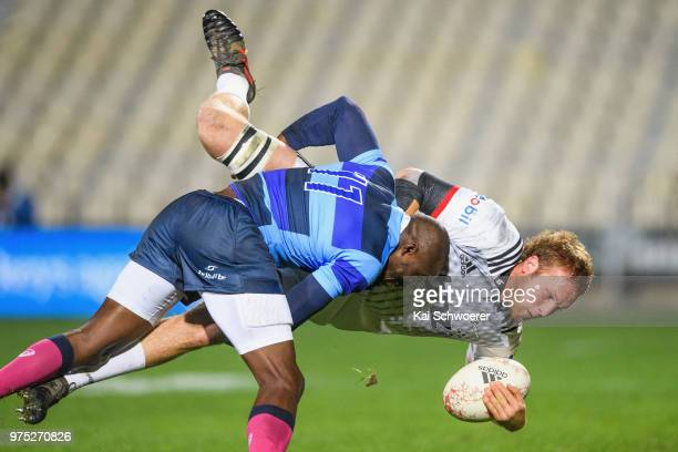 Mitchell Dunshea of the Crusaders is tackled by Djibril Camara of the French Barbarians during the match between the Crusaders and the French...