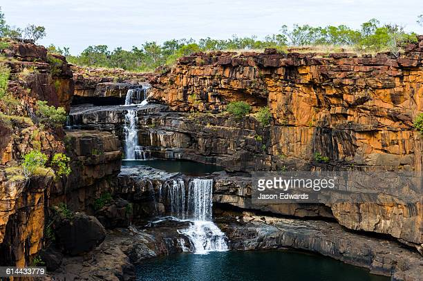 The magnificent Mitchell River cascades down ochre sandstone tiers in multiple waterfalls.