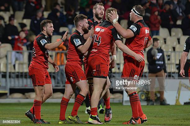 Mitchell Hunt Mitchell Drummond Luke Romano Johnny McNicholl and Wyatt Crockett of the Crusaders celebrate after Johnny McNicholl scores a try during...