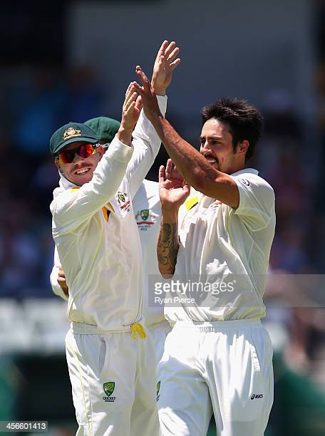 Mitchell Johnson and David Warner of Australia celebrate after Johnson took the wicket of Ben Stokes of England during day three of the Third Ashes...
