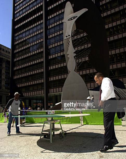 Mitchell Johnson hits his return to playing partner Marvin McBride while playing pingpong on a round revolving table in Chicago's Daley Plaza 4...