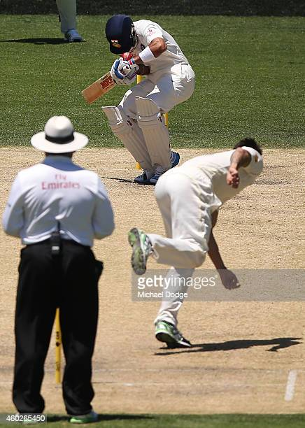 Mitchell Johnson of Australia bowls the ball and hits Virat Kohli of India on the helmet during day three of the First Test match between Australia...