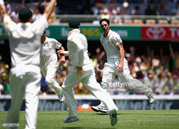 Mitchell Johnson of Australia celebrates after taking the wicket of Jonathan Trott of England during day two of the First Ashes Test match between...