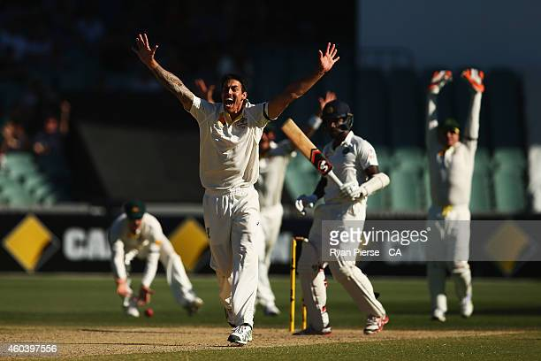 Mitchell Johnson of Australia celebrates after taking the wicket of Varun Aaron of India during day five of the First Test match between Australia...