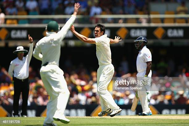 Mitchell Johnson of Australia celebrates dismissing Jonathan Trott of England during day two of the First Ashes Test match between Australia and...