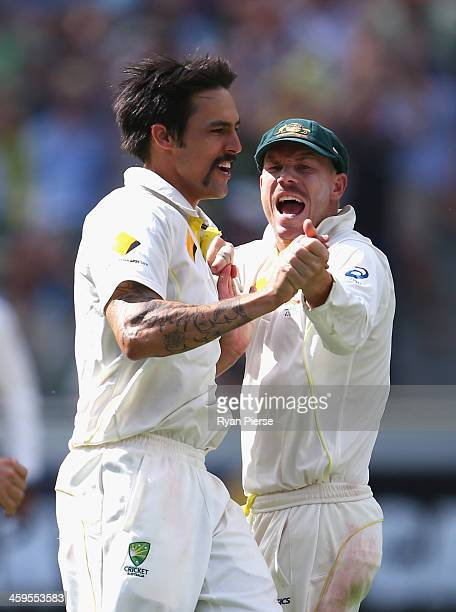 Mitchell Johnson of Australia celebrates with David Warner of Australia after taking the wicket of Jonny Bairstow of England during day three of the...