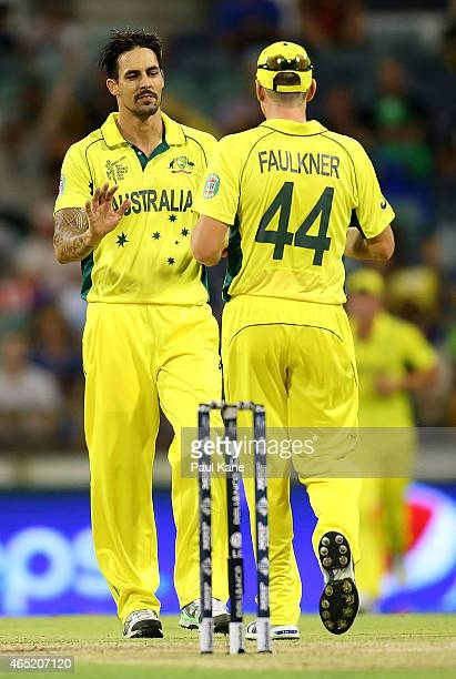 Mitchell Johnson of Australia celebrates with James Faulkner after dismissing Usman Ghani of Afghanistan during the 2015 ICC Cricket World Cup match...