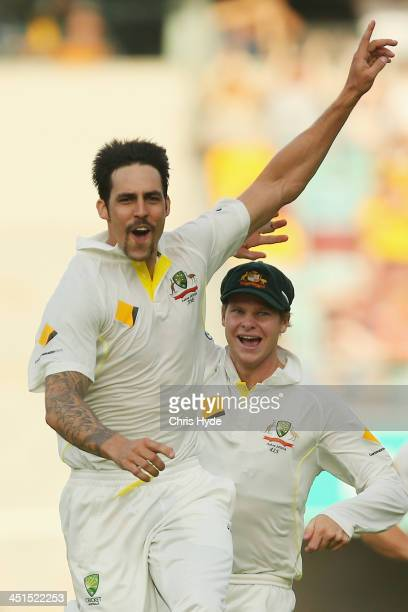 Mitchell Johnson of Australia celebrates with team mate Steve Smith after dismissing Jonathan Trott of England during day three of the First Ashes...