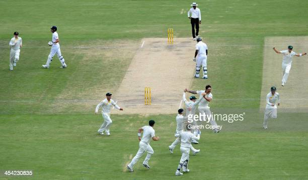 Mitchell Johnson of Australia celebrates with teammates after dismissing England captain Alastair Cook during day four of the Second Ashes Test Match...