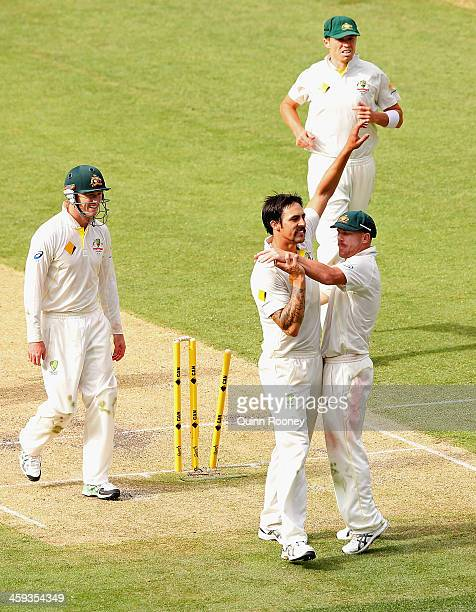 Mitchell Johnson of Australia is congratulated by David Warner after taking the wicket of Jonny Bairstow of England of England during day one of the...