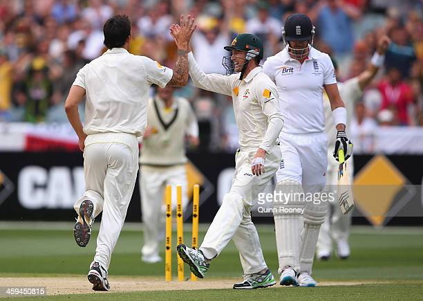 Mitchell Johnson of Australia is congratulated by George Bailey after taking the wicket of Kevin Pietersen of England during day two of the Fourth...
