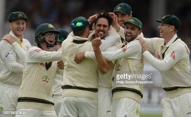 Mitchell Johnson of Australia is congratulated by teammates after dismissing England batsman Joe Root for 1 during the 2nd Ashes Test match between...