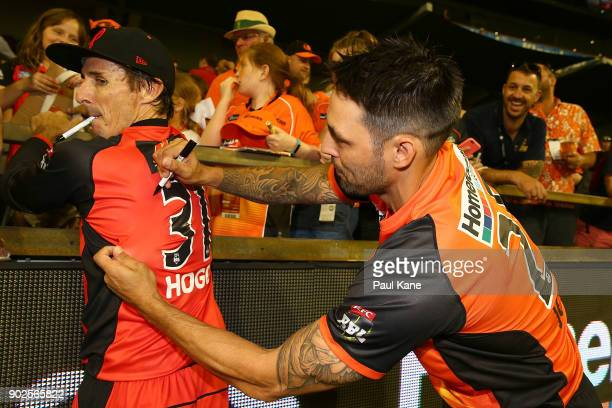 Mitchell Johnson of the Scorchers pretends to sign the playing shirt of Brad Hogg of the Renegades during the Big Bash League match between the Perth...