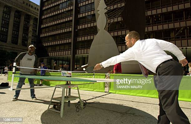 Mitchell Johnson stretches to make a return while playing pingpong on a round revolving table against Marvin McBride in Chicago's Daley Plaza 04...