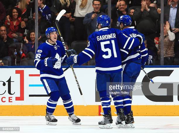 Mitchell Marner and Jake Gardiner of the Toronto Maple Leafs celebrate a goal by Alexey Marchenko during an NHL game against the Detroit Red Wings at...