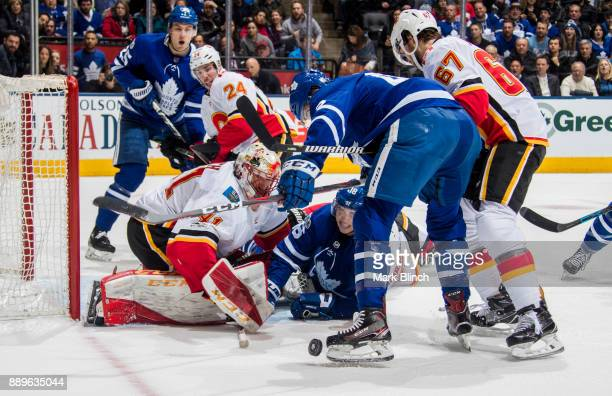 Mitchell Marner Nazem Kadri and Tyler Bozak of the Toronto Maple Leafs go to the net against Mike Smith and Travis Hamonic of the Calgary Flames...