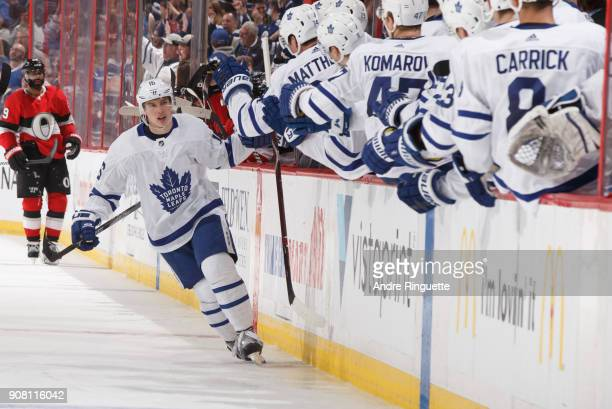 Mitchell Marner of the Toronto Maple Leafs celebrates his third period goal against the Ottawa Senators with teammates at the players bench at...