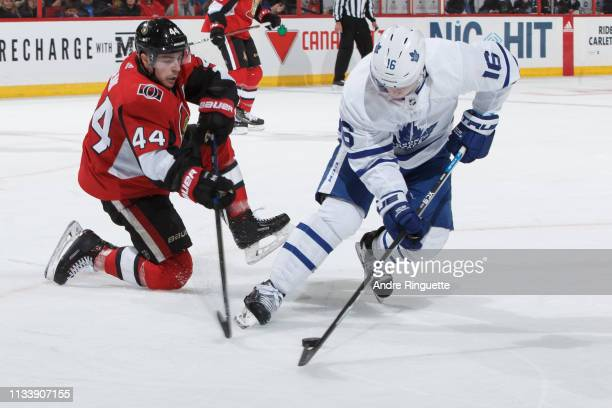 Mitchell Marner of the Toronto Maple Leafs stickhandles the puck against JeanGabriel Pageau of the Ottawa Senators at Canadian Tire Centre on March...