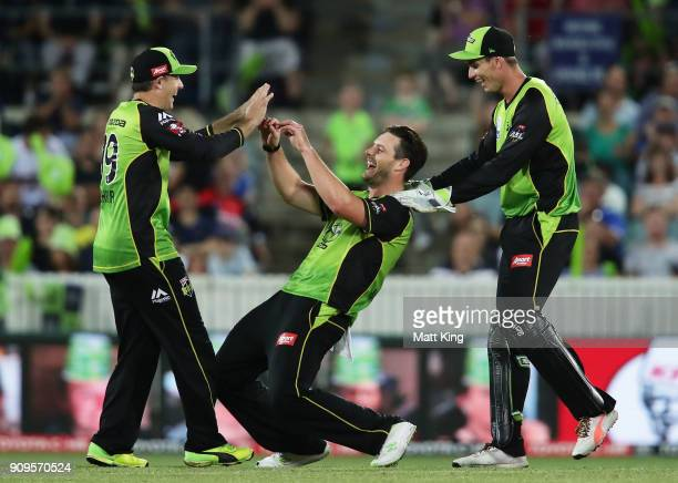 Mitchell McClenaghan of the Thunder celebrates with team mates after taking the wicket of Dwayne Bravo of the Renegades during the Big Bash League...
