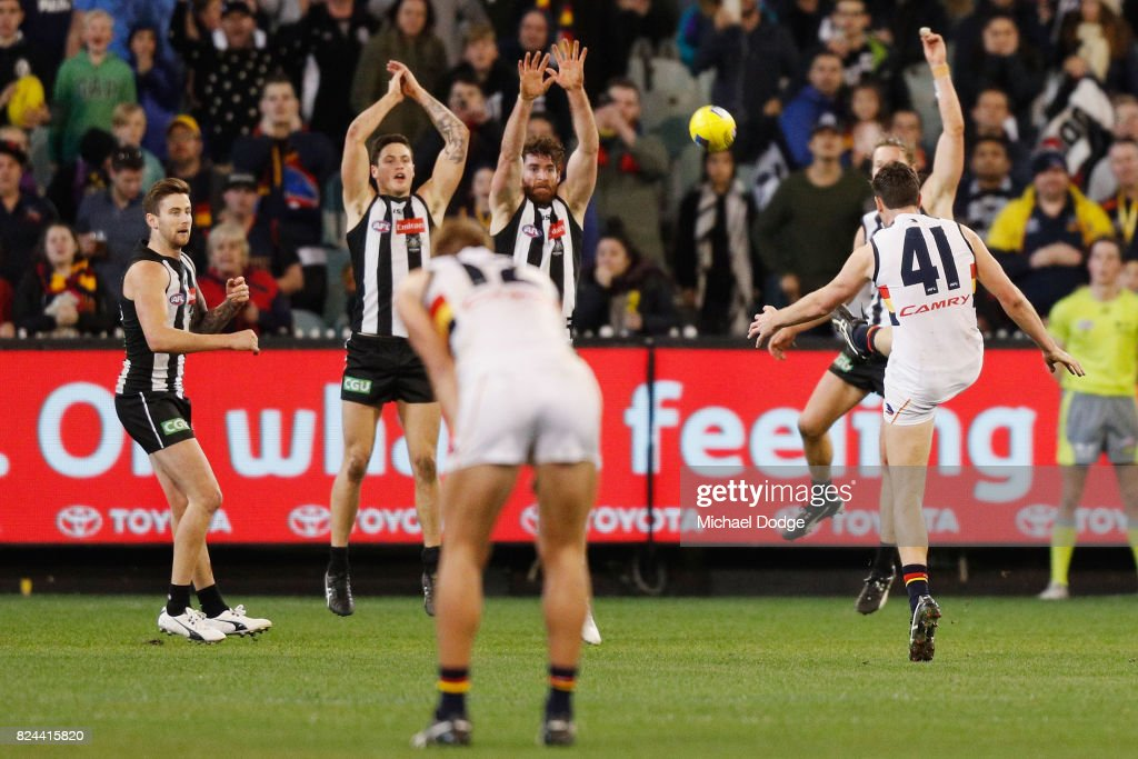 Mitchell McGovern of the Crows kicks the ball for a goal over Tyson Goldsack of the Magpies to seal a draw during the round 19 AFL match between the Collingwood Magpies and the Adelaide Crows at Melbourne Cricket Ground on July 30, 2017 in Melbourne, Australia.