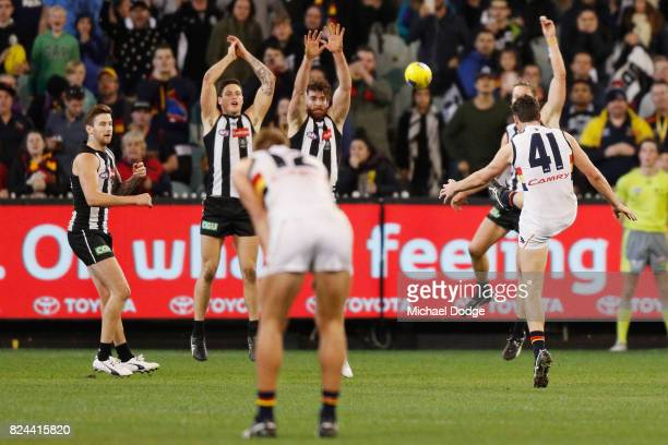 Mitchell McGovern of the Crows kicks the ball for a goal over Tyson Goldsack of the Magpies to seal a draw during the round 19 AFL match between the...