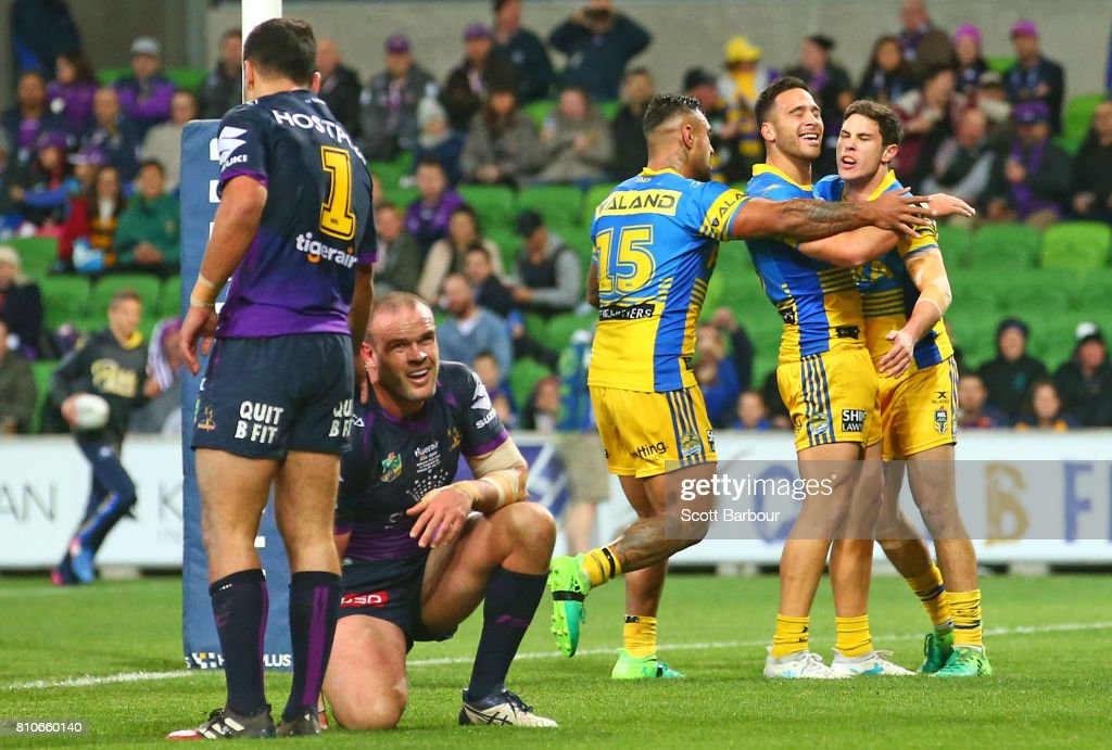Mitchell Moses of the Eels is congratulated by his teammates after scoring a try as Nate Myles of the Storm looks on during the round 18 NRL match between the Melbourne Storm and the Parramatta Eels at AAMI Park on July 8, 2017 in Melbourne, Australia.