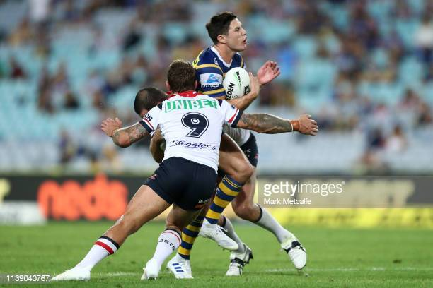 Mitchell Moses of the Eels is tackled by Jake Friend of the Roosters and Boyd Cordner of the Roosters during the round three NRL match between the...