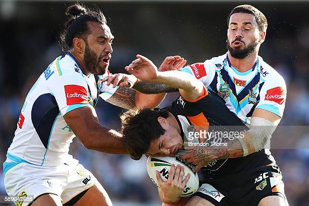 Mitchell Moses of the Tigers is tackled by the Titans defence during the round 23 NRL match between the Wests Tigers and the Gold Coast Titans at...